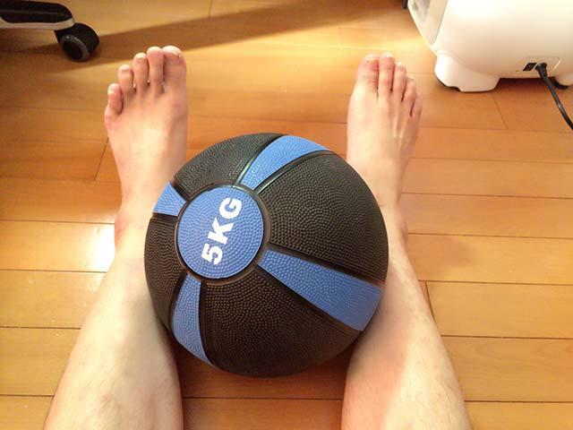 硬いメディシンボールを足に挟んでみます